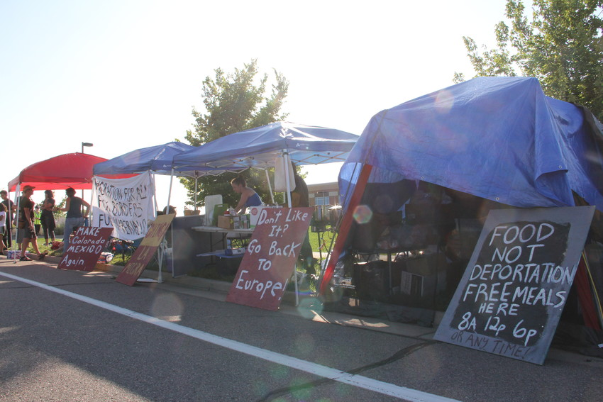 A group of protesters stands July 31 amid signs at the U.S. Immigration and Customs Enforcement (ICE) Denver Field Office at 12445 E. Caley Ave. in Centennial. Protesters set up an encampment and planned to stay for a week.