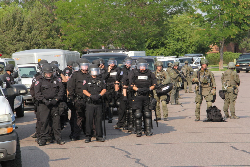 Deputies and SWAT personnel from the Arapahoe County Sheriff's Office line up on East Caley Avenue in front of the U.S. Immigration and Customs Enforcement (ICE) Denver Field Office Aug. 2. Protesters formed blockades at entrances to the parking lot.