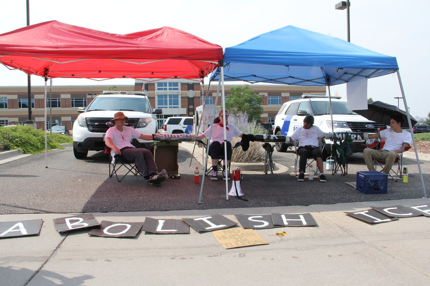 "Signs that spell ""Abolish ICE"" and one reading  ""No human is illegal"" in front of the U.S. Immigration and Customs Enforcement (ICE) Denver Field Office Aug. 2. Protesters formed blockades at entrances to the parking lot."
