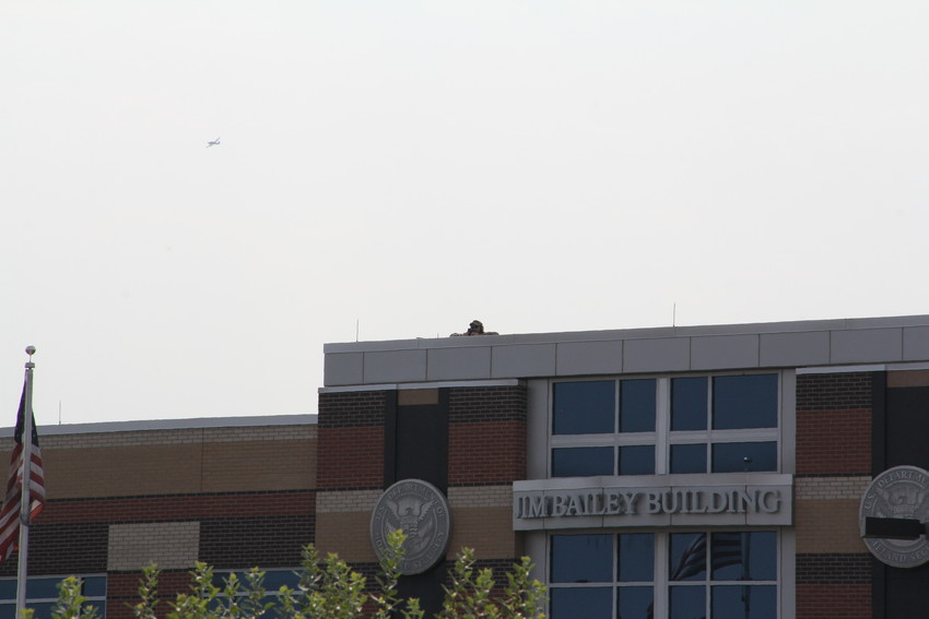 A law-enforcement official on the roof at the U.S. Immigration and Customs Enforcement (ICE) Denver Field Office Aug. 2. Another official was on the roof at the building across the street amid a protest at the ICE office.