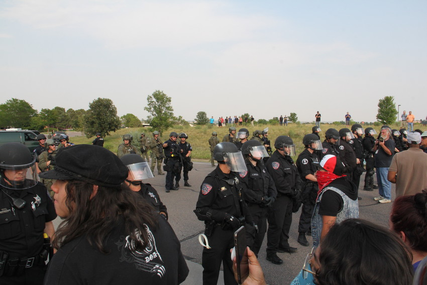 In the distance, on the hill, people gathered to watch the scene at the U.S. Immigration and Customs Enforcement (ICE) Denver Field Office Aug. 2. Protesters blocked entrances at the parking lot.