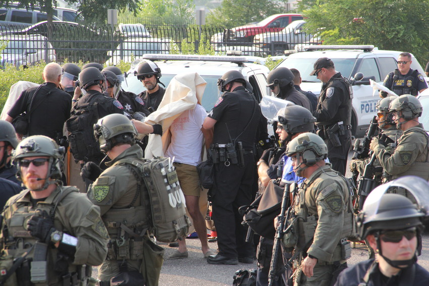 "One of the protesters who blocked entrances at the parking lot at the U.S. Immigration and Customs Enforcement (ICE) Denver Field Office Aug. 2 in Centennial. The protester's shirt reads, ""Abolish ICE."" Protesters were covered by sheets as officers removed the material that linked their arms."