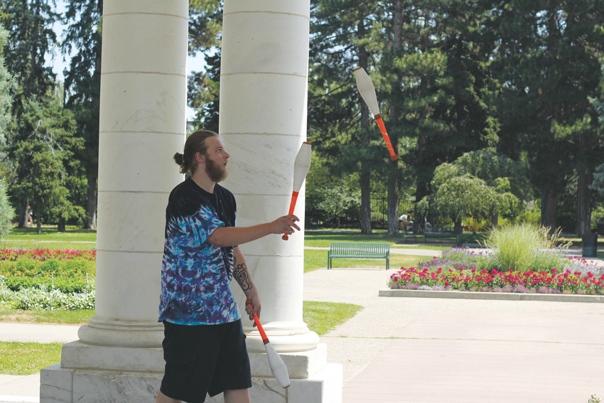 Taylor Buuck practices juggling at the Cheesman Park Pavilion. He and his friends meet at the Pavilion area frequently to listen to music and juggle bowling pins.
