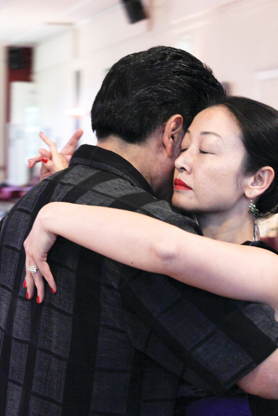 Xiaoli Quispe leans against her husband Jorge as they dance during an open dance session with Tango Colorado. The pair dance close-embrace style tango and have traveled the world performing.