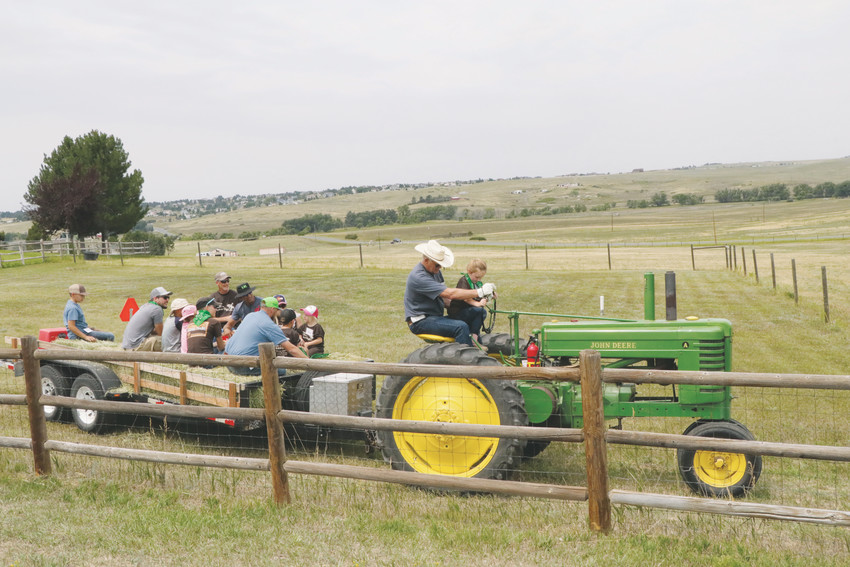 Children of first-responders, military personnel and veterans take a hay ride around the arena during Aug. 1 Buckaroo Day at Eagles Nest Ranch.