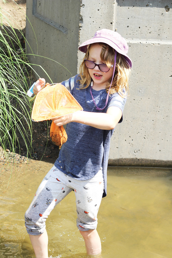 A child from the Denver Tour Club summer camp scoops up dirt from the creek in Washington Park, searching for crawdads. The Denver Tour Club frequently spends time at the neighborhood park.