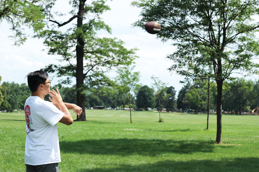 A man throws a football at Washington Park, enjoying a summer day with his friends.