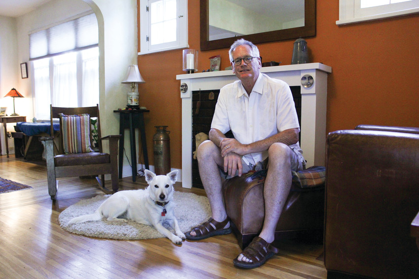 Tim O'Byrne and his dog Oliver sit in the living room of his home in Washington Park West. His home was built in 1929.