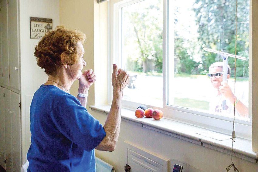 A homeowner watches as a volunteer from A Little Help cleans her windows.