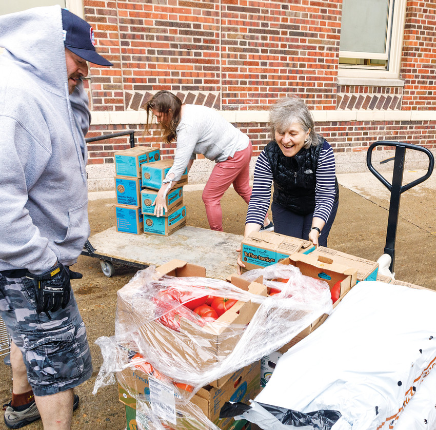 Matthew Karm, left, helps Jaclyn Yelich unload tomatoes at South High School. We Don't Waste partnered with Food for Thought to make sure the school's food pantry had fresh food items for students.