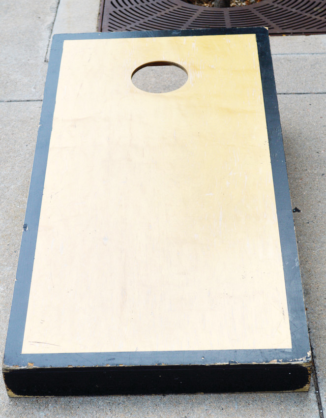 Cornhole boards are 48 inches by 24 inches and made from 1/2-inch plywood. The front of the platform stands 2 1/2 to 4 inches tall and the back of the platform sits 12 inches off the ground. Many board designs are customized and stained but many others just have decals on them.