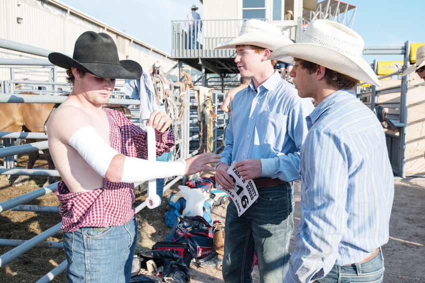 Riders Cole Reiner, Ian McGivney and Dylan Sandwick get prepped for the rodeo on Aug. 3.