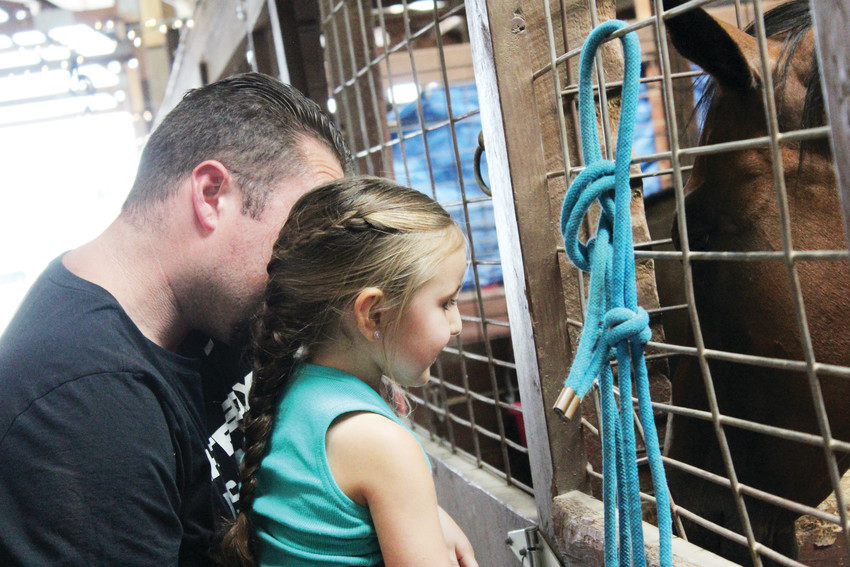 Paisley Jander, 3, and her father, Chris, greet one of the horses at the Douglas County Fair and Rodeo Aug. 4.