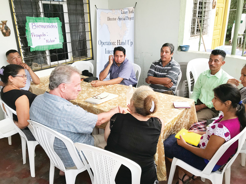 Parker businessman Lanny York, in the gray shirt, meets with members of the local church during one of his mission trips to Honduras. York founded and heads Operation Hands Up International, which partners with Honduran churches providing poor families with hens, roosters and the equipment to establish a chicken flock.