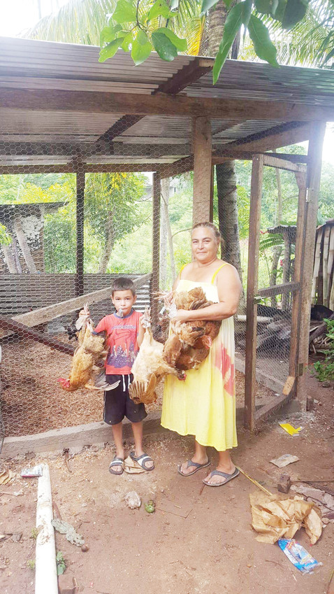 A Honduran woman and her son hold two of the chickens they received from Project Poultry.  Project Poultry is an outreach to help poor families in rural Honduras, headed by Parker businessman Lanny York and his organization Operation Hands Up International.