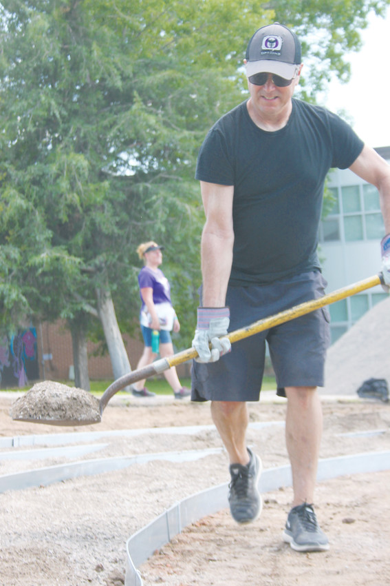 "Options Secondary Program principal Greg Sumlin spreads gravel in the school's new ""serenity garden"" while science teacher Kerry Nixon supervises. ""A garden like this dovetails with who we are as a school,"" Sumlin said. ""We're all about trying different things."""