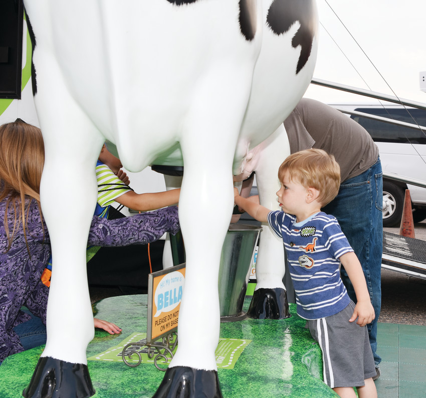Landon Lancaster, 2, of Thornton, tries to milk a simulated cow at the Dairy Max exhibit Aug. 1 at 2018's Adams County Fair.
