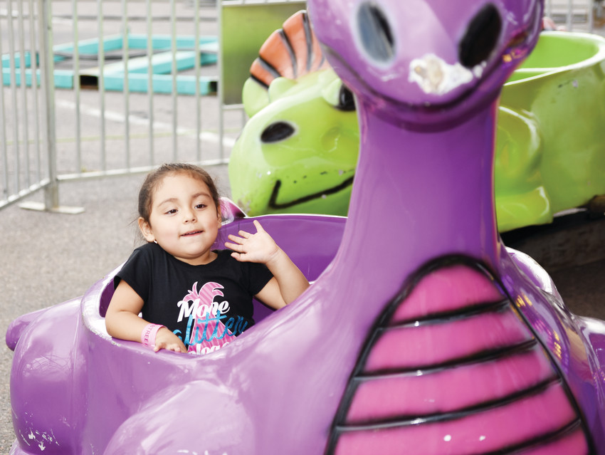 Daleyca Ortega, 3, of Commerce City, enjoys a kids' dinosaur ride on the first day of the Adams County Fair Aug. 1 at Adams County Regional Park.