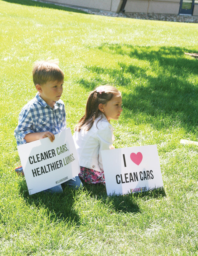 Two children listen as community members and elected officials speak at a July 31 press conference in Lakewood opposing the Trump administration's rollback of clean car standards.
