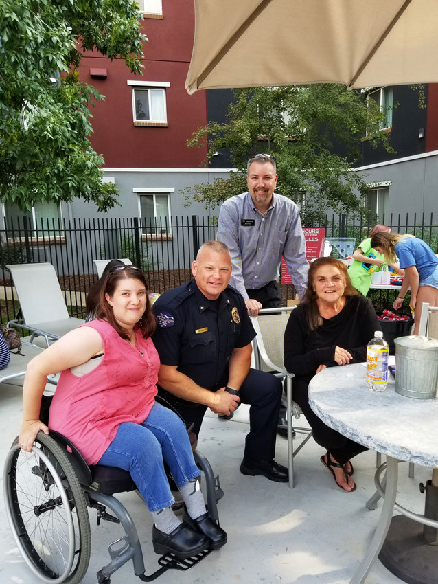 Commander Eric Kellog and Councilman Bob Fifer visit with Arvada residents Phelan Hug and Andrea Tortorici at the Market Place National Night Out celebration.