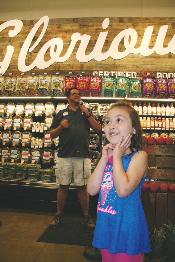 Madilynn Magallan, 5, the granddaughter of Antoinette Skul, the office manager for the Lucky's Market at 3545 Wadsworth Boulevard, waits with excitement for the Aug. 8 grand opening ceremony of the store.