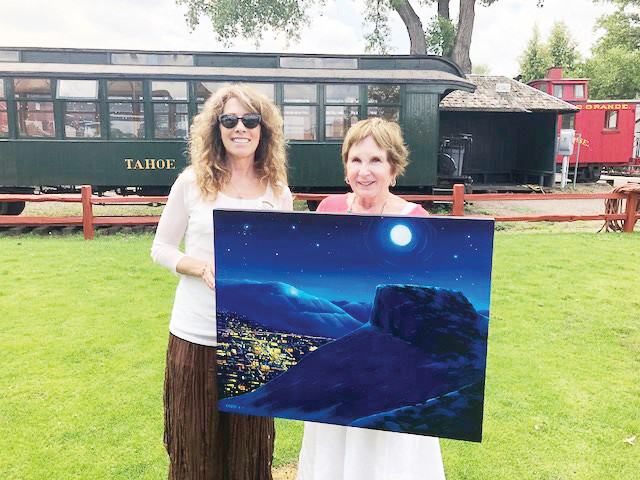 The Golden Chamber of Commerce's CEO Leslie Klane, left, and Golden Mayor Marjorie Sloan display this year's art, designed by local artist Jesse Crock, that will appear on the 2018 Golden Fine Arts Festival posters and T-shirts. The 28th annual Golden Fine Arts Festival takes place Aug. 18 and 19.