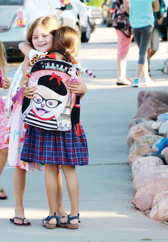 Madison Ross, 7, embraces Emily Kozlovic, 7, at the first day of school on Aug. 9. They are second graders at Cougar Run Elementary in Highlands Ranch.