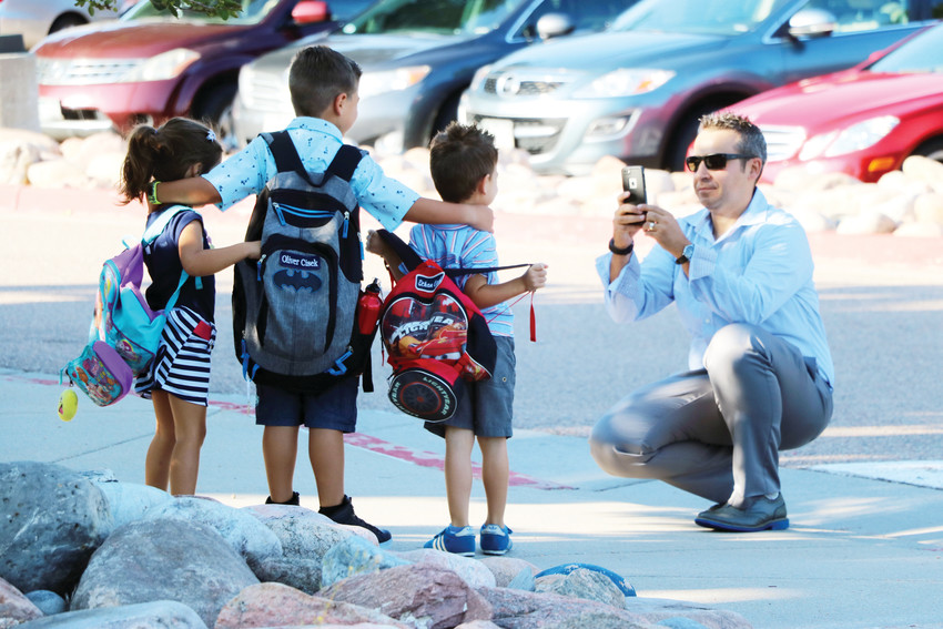 Parent Thomas Cisek snaps a photo of his kids, 6-year-old Oliver and 4-year-old twins Stella and Ethan, at Cougar Run Elementary's first day of school on Aug. 9. The Highlands Ranch school buzzed with parents and kids.