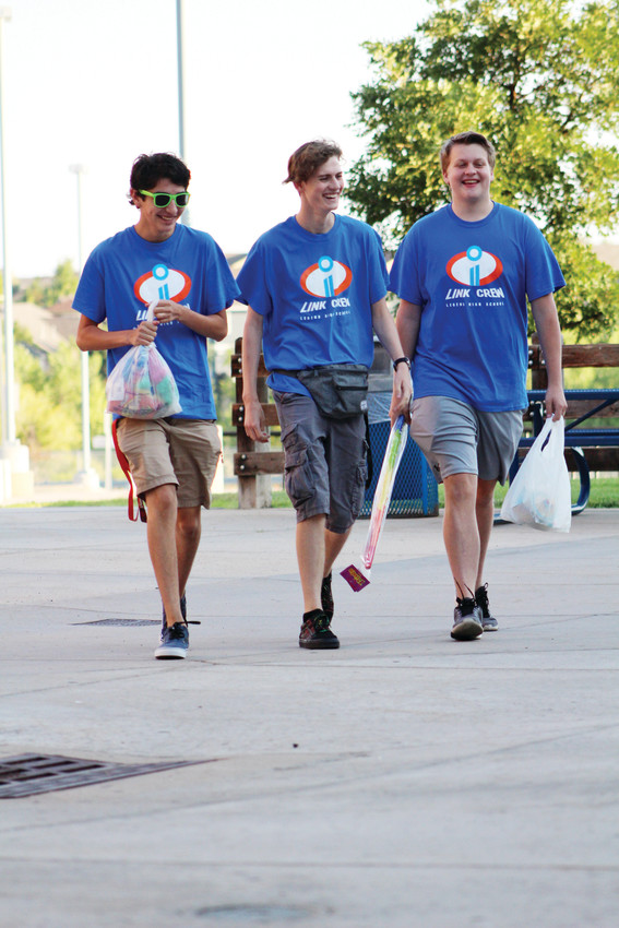 "Three members of the ""Link Crew,"" non-freshman student leaders, walk onto campus for the first time of the new school year at Legend High School. The Link Crew help freshmen get acclimated to high school life during orientation."