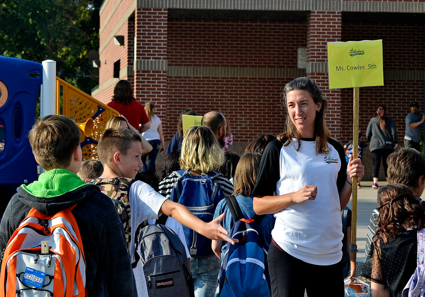 Fifth grade teacher Emily Cowles greets students as they enter Stevens Elementary for the first day of school Thursday, Aug. 16.
