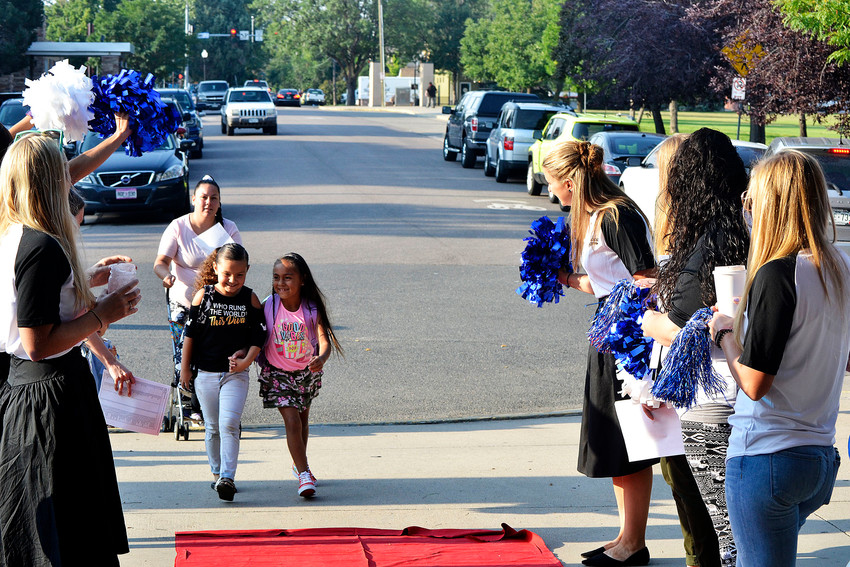 Jacqueline Martinez (left) and Liyahna Lucero enter Stevens Elementary on red carpet and surrounded by cheers on the first day of school in Wheat Ridge. The two friends started second grade.