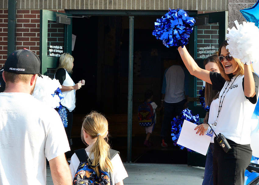 Desiree Mericle, school dean, cheers students and parents as they enter Stevens Elementary in Wheat Ridge for the first day school.