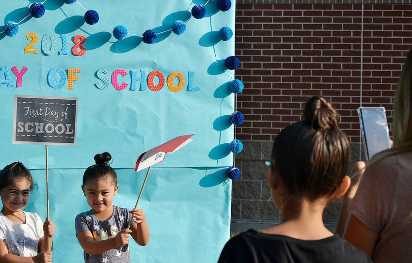 Raquel Avila (far right) takes a picture of Zaria and Ariel, both in pre-kindergarten, during first day of school activities at Stevens Elementary in Wheat Ridge.