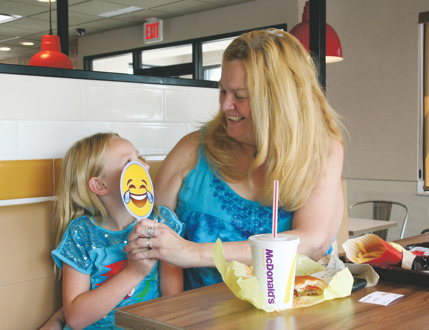 Paula Gaer and her family friend Lily, 6, enjoy lunch at the Applewood McDonald's restaurant on Aug. 15. The two got to spend the day together before Lily starts the first grade.