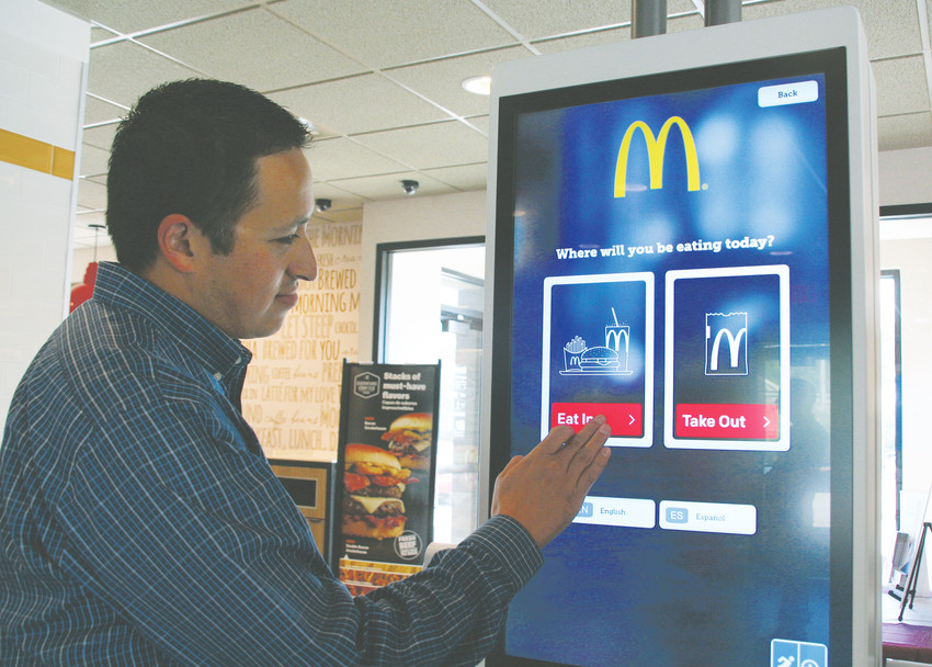 Mike Sandoval, a local franchisee who co-owns and operates eight McDonald's restaurants in the metro area along with his father Frank, demonstrates how to use the Applewood McDonalds' new digital self-order kiosk.