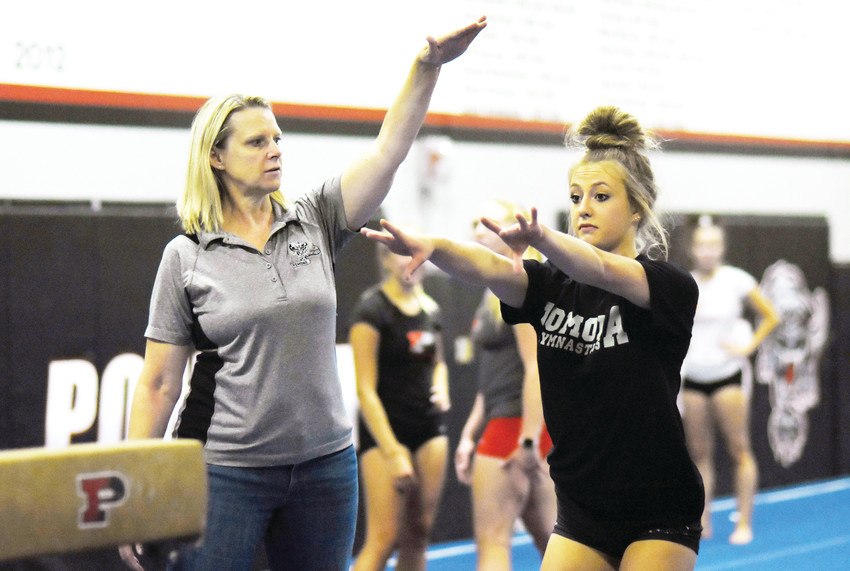 Pomona coach Tracey Boychuk, left, works with Pomona senior Brooke Weins during practice. Weins has battled through injuries since winning the Class 5A all-around individual state championship two years ago as a sophomore.