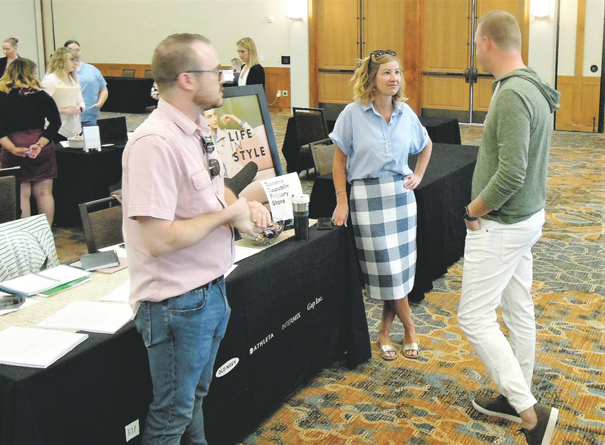 Banana Republic Assistant Manager Daniel Worsham, District Manager Susan Stone and general manager Ben Blasinsky, chat while waiting to talk to prospective new employees Aug, 17 at a Denver Premium Outlets job fair in Westminster.