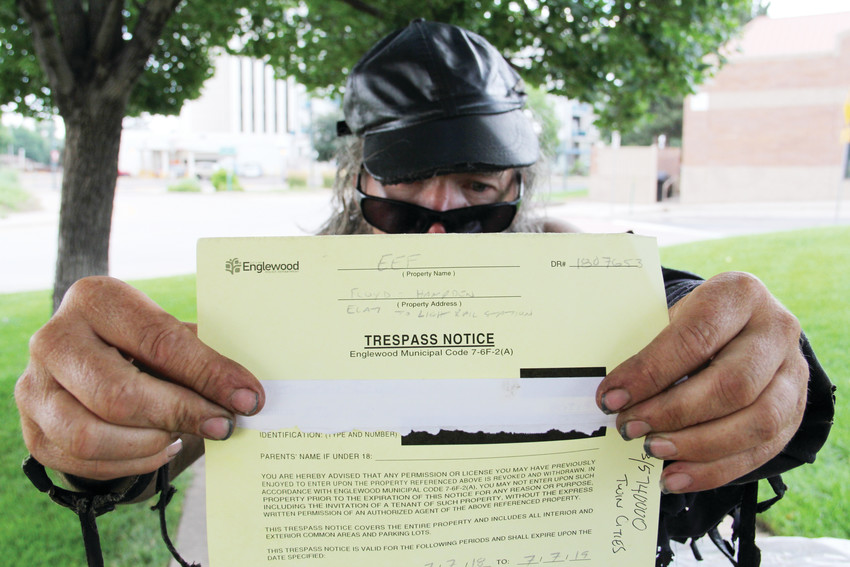 Randall Thompson, a man who has been homeless for 5 1/2 years in the Denver metro area, holds up a trespass notice he was issued on July 7 near the Englewood Civic Center, 1000 Englewood Parkway. He stood three blocks to the east, now banned from that area. Thompson, in his late 50s, frequently comes to the CityCenter Englewood shopping center along West Hampden Avenue, a few blocks west of South Broadway.