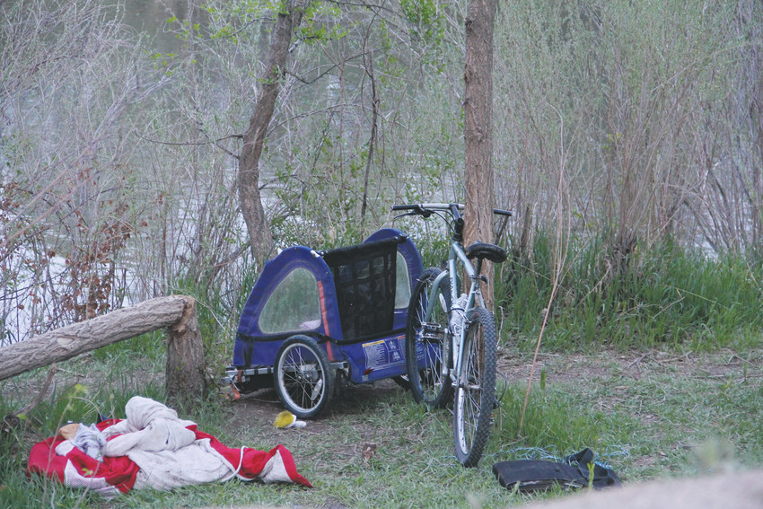A bike and other belongings near a camp site on the Denver side of the South Platte River — Englewood is on the east side for a stretch— near West Dartmouth Avenue May 6. At least two people sat at the camp site that evening. One, a middle-aged man who has been homeless and camping on the river for four years, said the number of campers has more than doubled in the past two years. The man, who did not want to be named, has spent time along the river between West Mississippi to Quincy avenues. It stretches through Sheridan, Englewood and Denver in that distance.