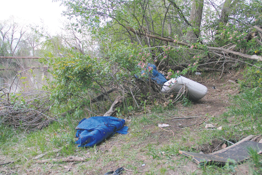 Blankets and a cushion drape the branches along the east banks of the South Platte River near West Dartmouth Avenue May 6. A worn walkway leads to the clearing.