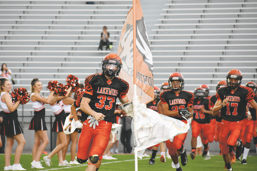 Lakewood senior Kegan Hufford (33) carries the Tigers' flag as players storm the field Friday, Aug. 24, at Jeffco Stadium in the Tigers' season opener against Bear Creek. Lakewood won 38-13 to start its 2018 campaign.