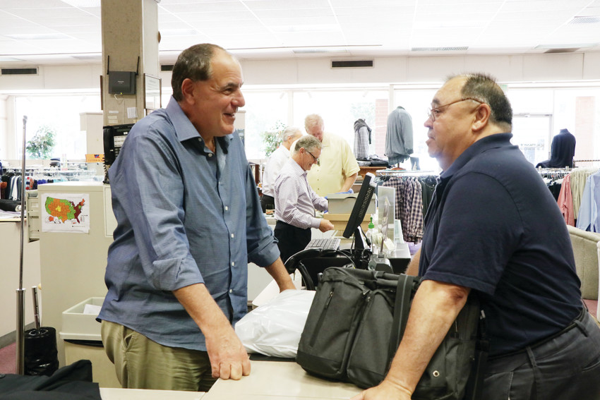 Sam Kaufman, left, owner of Kaufman's Tall & Big Shop, talks with former employee and now customer Mike Miller. The store was founded by Sam's dad Fred and is celebrating its 60th anniversary.