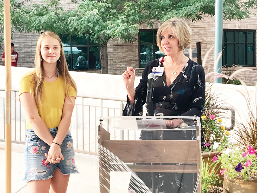 "Laci Van Loozen (left) is introduced by Marian Savitsky during Sky Ridge's 15th anniversary. Van Loozen was the first baby delivered at the hospital and visits every five years for her's (and Sky Ridge's) birthday. She only lived in Colorado for about two years before her family moved outside Austin, Texas, but she always tells her parents she wants to move back because ""it's so much prettier."""