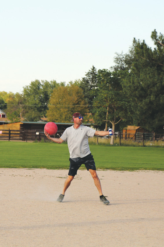 Tanner Glanz, of the Arvada Young Professionals team, balances out his throw to first with the beer in his left hand.