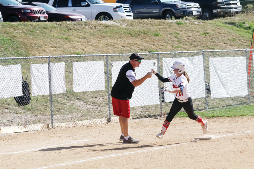 Elizabeth freshman catcher Elyssa Bain gets a high-five from her coach as she rounds third base after hitting a home run.