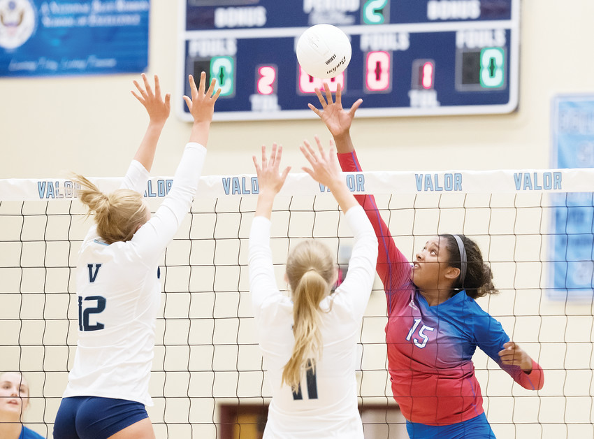 Cherry Creek's Carter Booth (15) stretches to get the tip as Valor Christian's Courtney Lane (12) and Miki Timlin set up for defense. Host Valor defeated Cherry Creek in three sets (25-19, 25-19, 25-21) Aug. 30. Cherry Creek fell to 1-2 on the season, while Valor improved to  3-0.