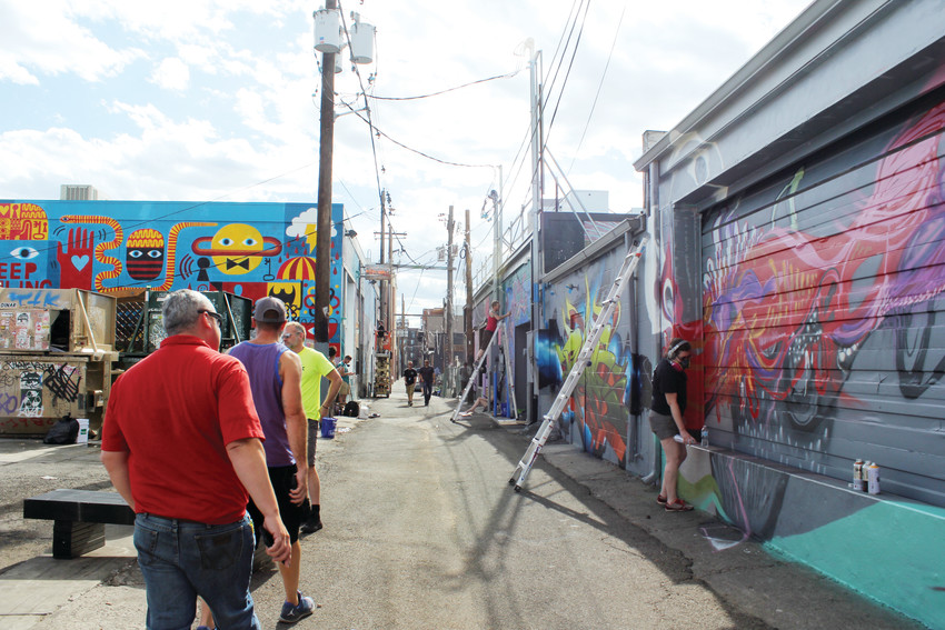 People walked through the alleys in the River North Art District during the 2017 Crush Walls event. The event brings artists in from around the world to paint large scale murals on buildings in RiNo.