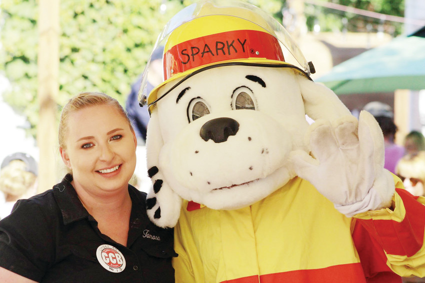 Tamara Sturdavant, Golden City Brewery's general manager, gets her picture taken with the Golden Fire Department's mascot Sparky during a previous year's GoldenFest. The annual fundraising event takes place on Sept. 8.