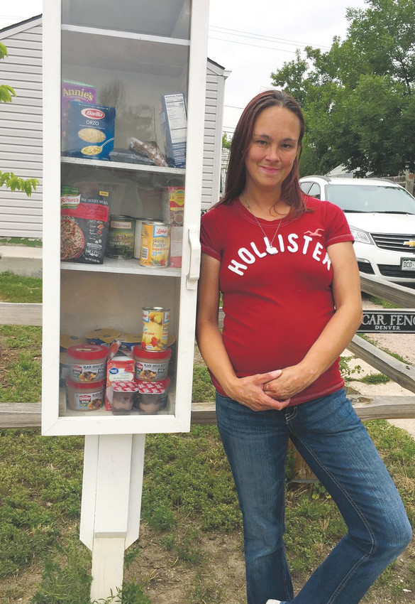 Deidra Bates stands with her food pantry box outside of her southwest Denver home, near South Federal Boulevard and West Exposition Avenue. Bates put up the box — stocked with non-perishable food items and basic necessities — to help fill a need in her community.
