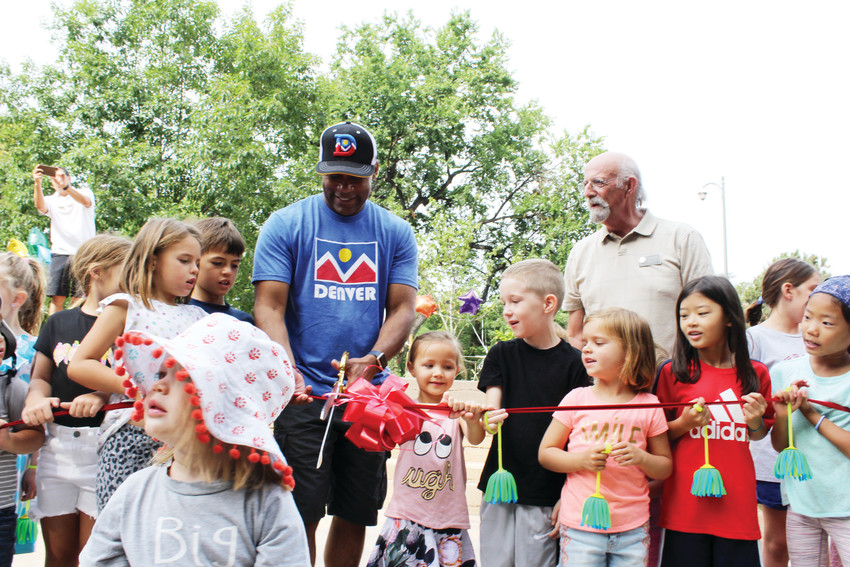 Mayor Michael B. Hancock invites children to help him cut the ribbon for the new playground at Washington Park. The playground opened on Aug. 18 between the two lakes. The old playground in the northern section of the park will now be decommissioned by the Denver Parks and Recreation Department.